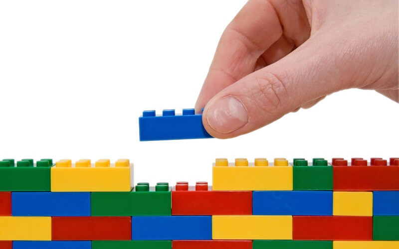hand building up a wall by stacking up lego
